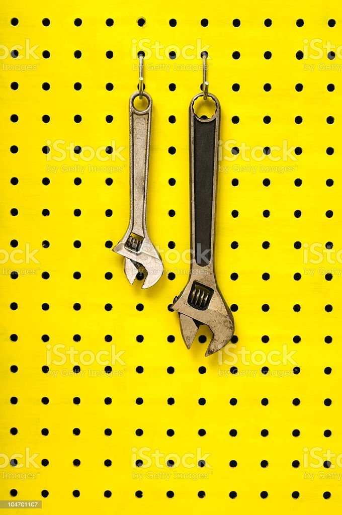 Two wrenches hang from hooks on yellow pegboard royalty-free stock photo