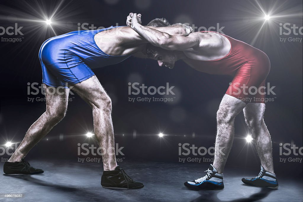 Two wrestlers in stance on stage stock photo
