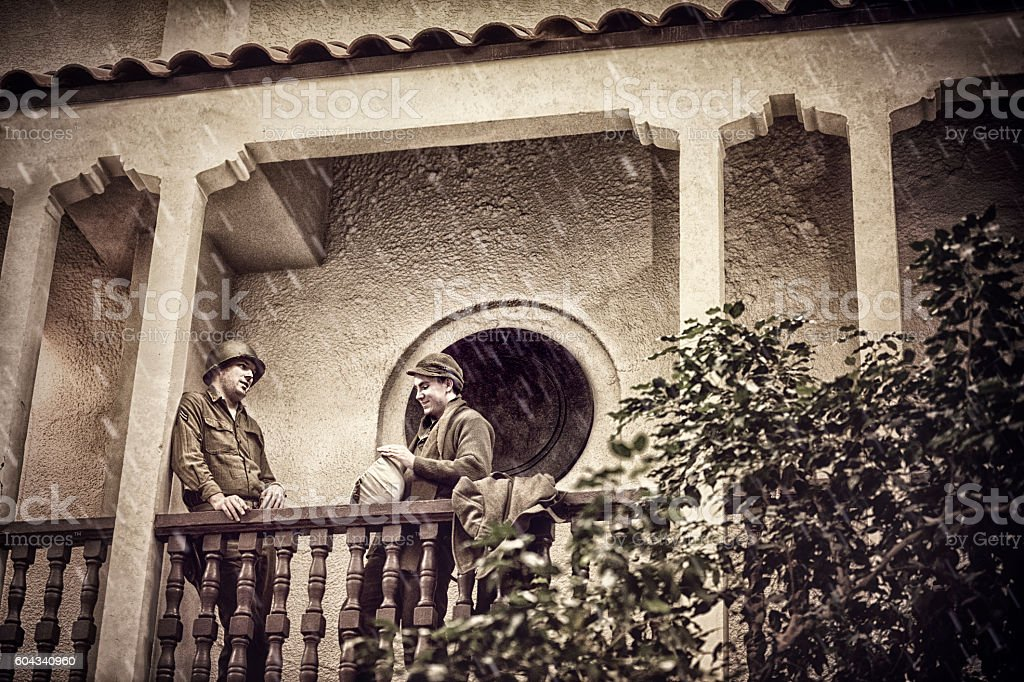 Two WWII US Infantry Soldiers Standing On A Balcony Talking stock photo