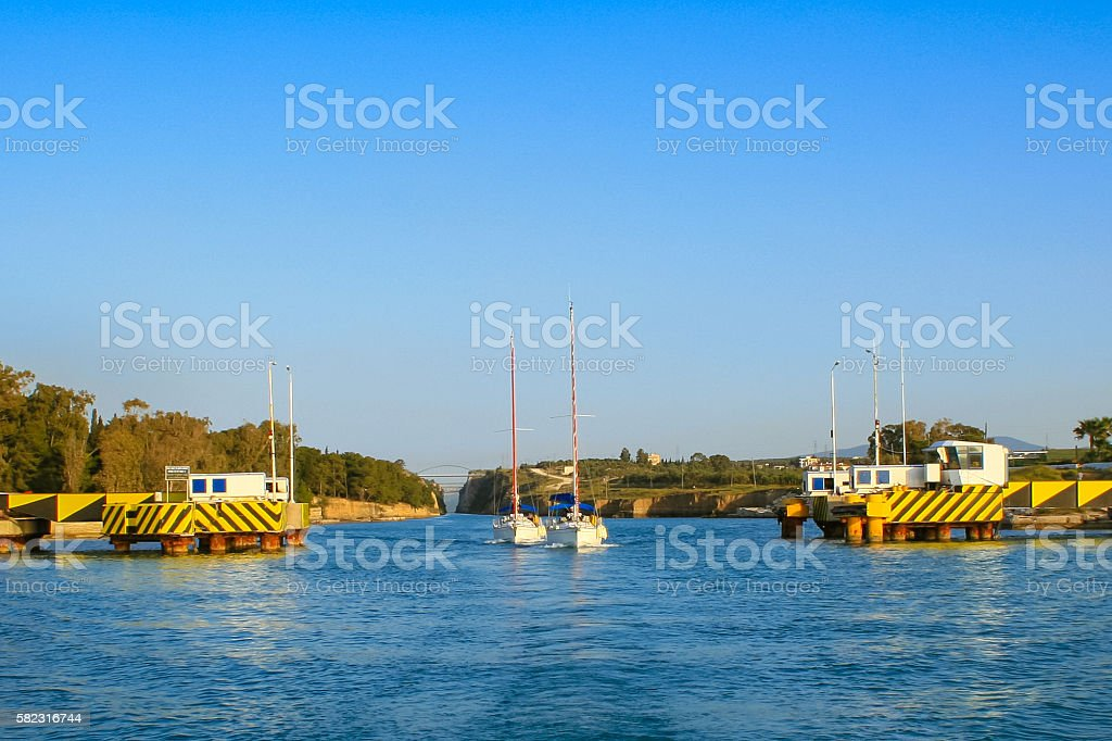 Two yachts exiting the Corinthian Canal gate in the evening. stock photo