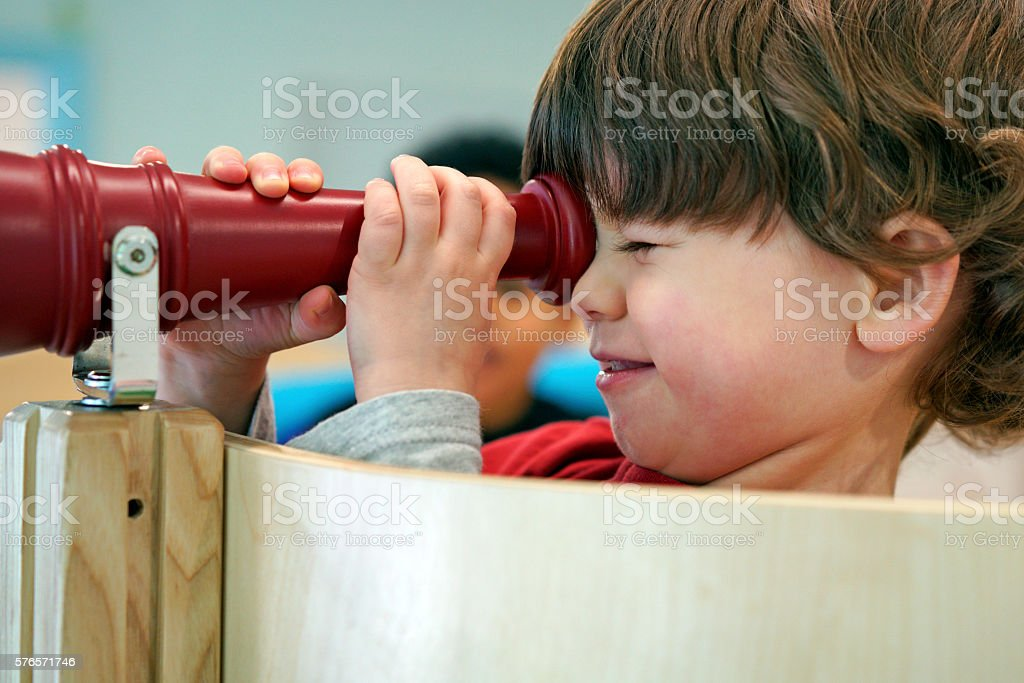 Two year old boy playing with toy telescope stock photo