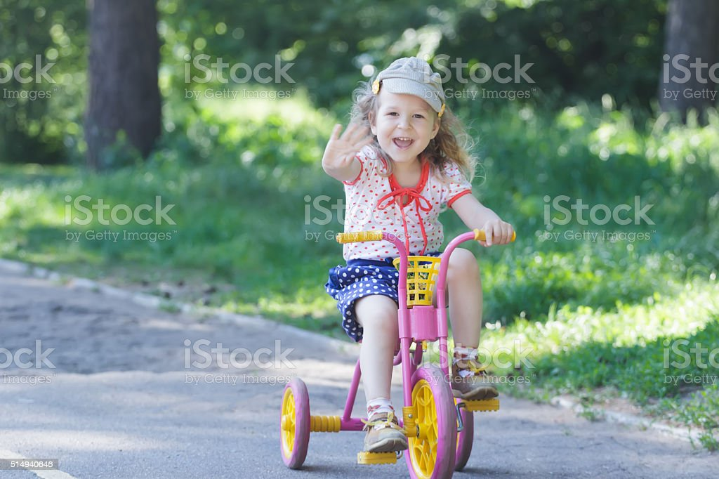 Two year-old laughing girl cycling kids pink and yellow tricycle stock photo