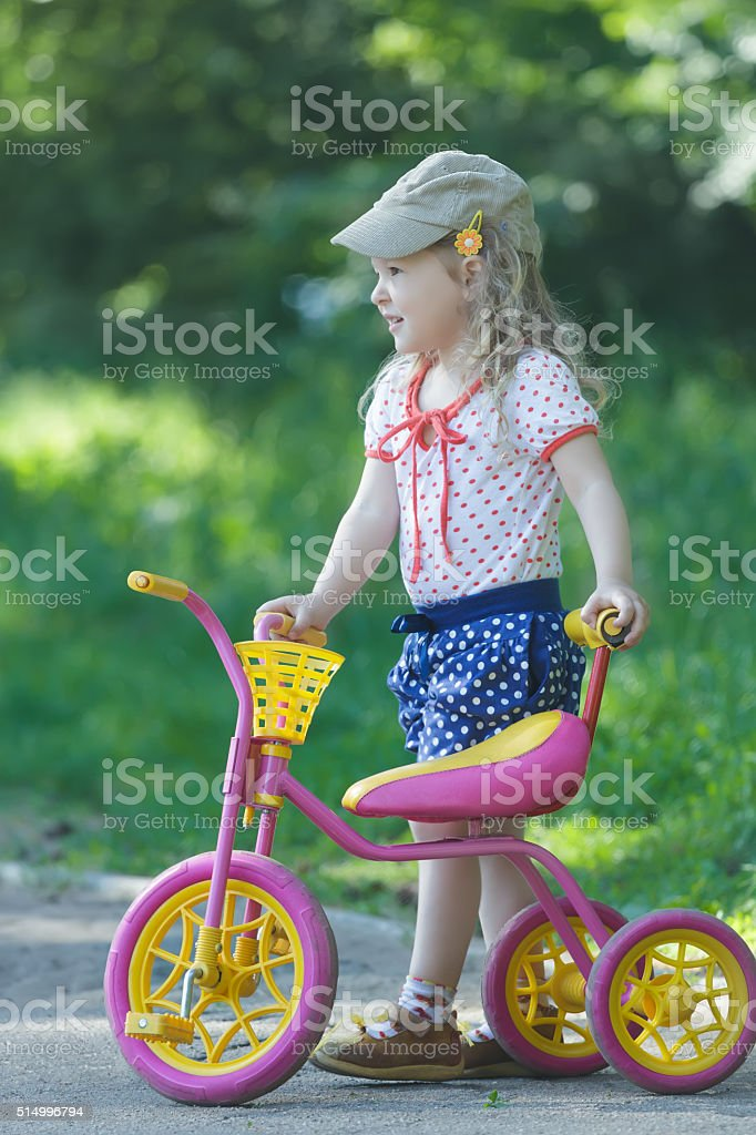 Two year-old standing near pink kids tricycle with steel frame stock photo