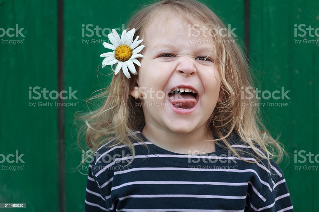 Two years old grimacing girl with chamomile flower in hair stock photo