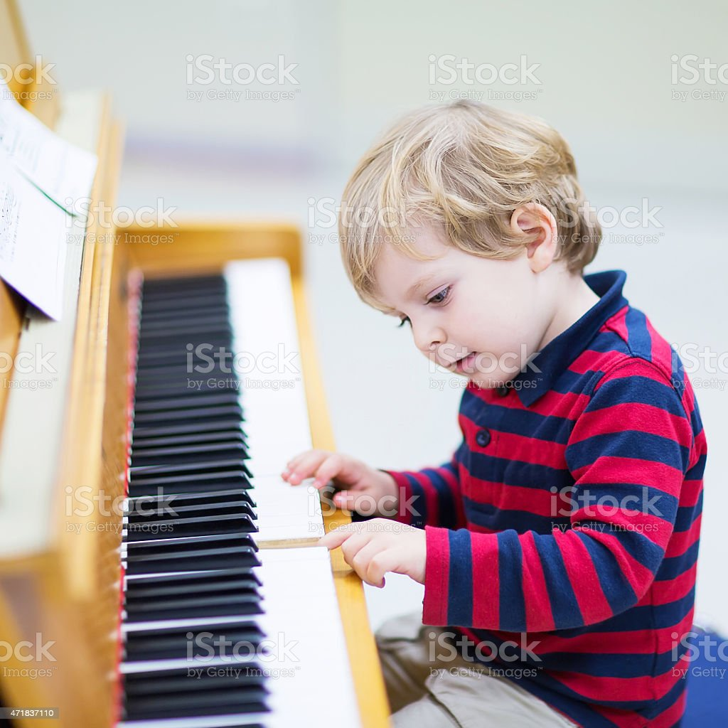 Two years old toddler boy playing piano, music schoool. stock photo
