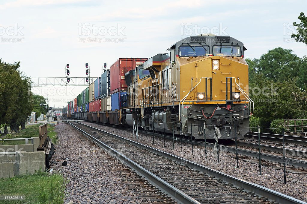 Two yellow locomotives and double stack freight train stock photo