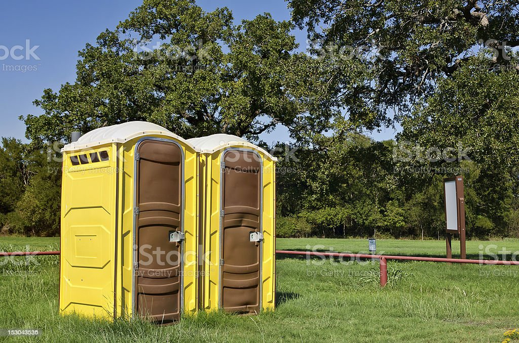 Two yellow portable toilets at a park stock photo