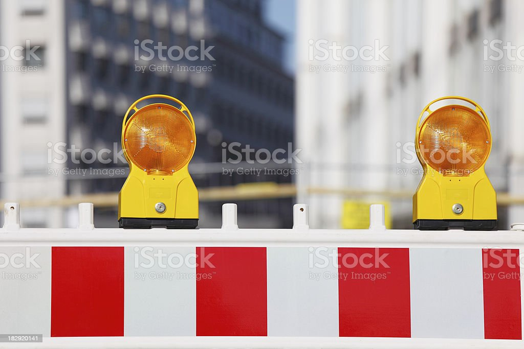 two yellow traffic warning lamps on barricade stock photo