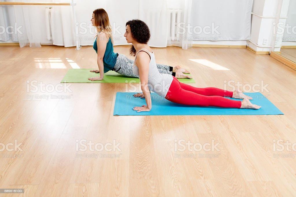 Two yogini practicing yoga and meditating in pose cobra stock photo