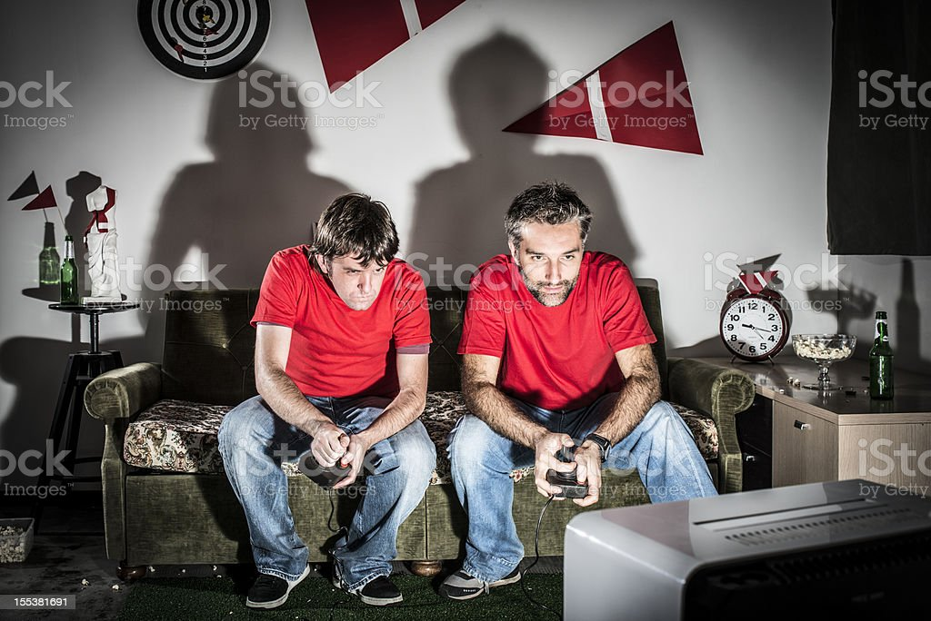 Two young adult brothers videogamer playing at night stock photo