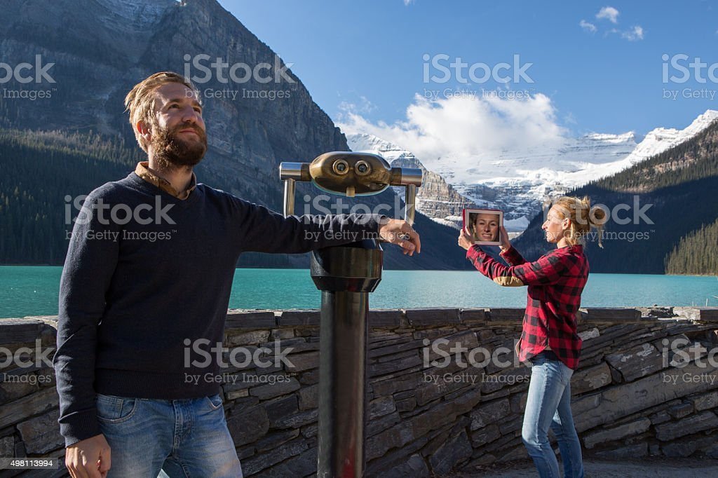 Two young adults at lake Louise enjoying the landscape stock photo