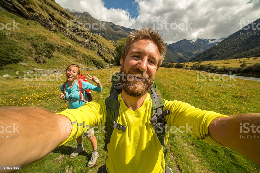 Two young adults hiking take self portrait in nature stock photo