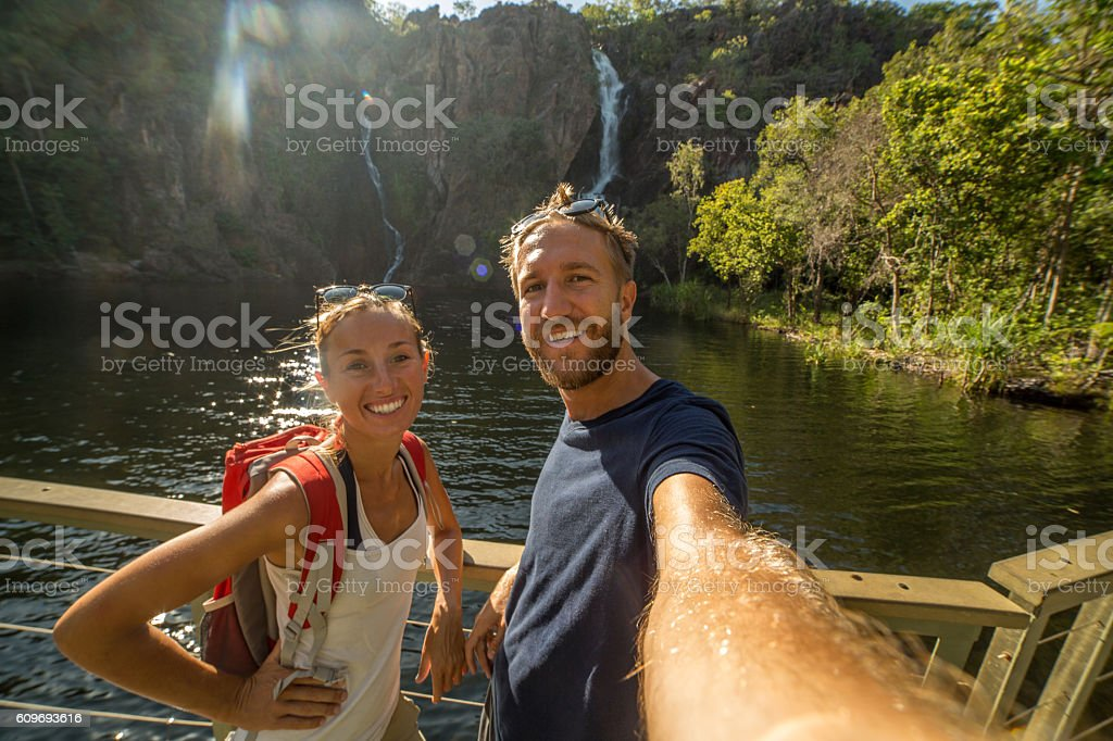 Two young adults on travel take selfie portrait, waterfalls stock photo