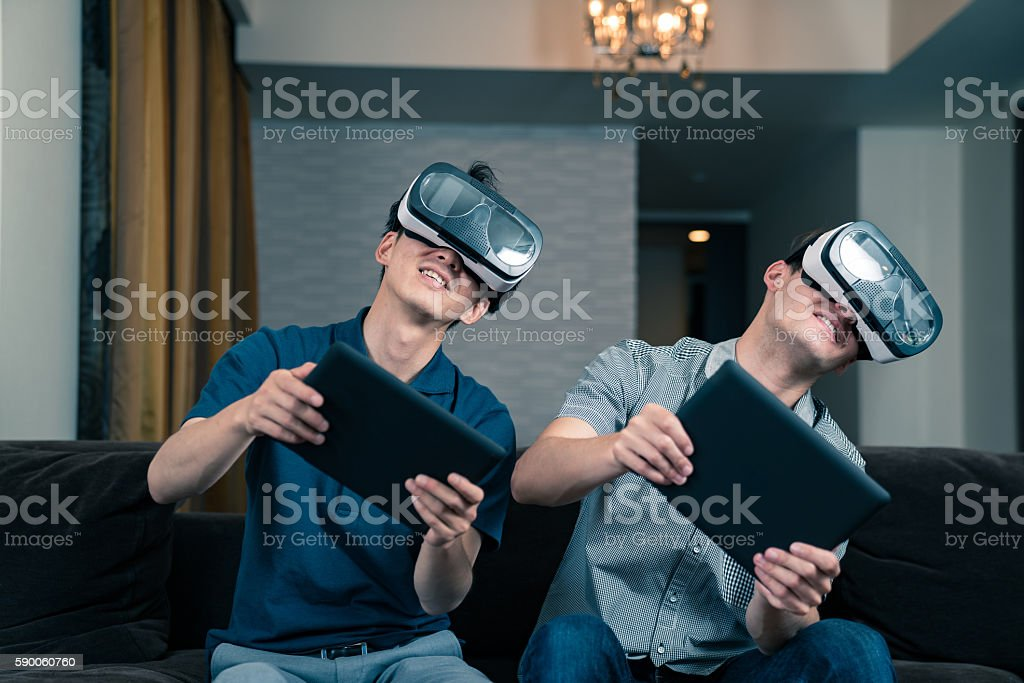 Two young adults playing games on virtual reality headsets stock photo