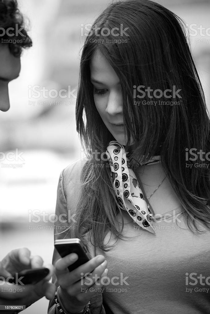 Two young adults sharing telephone contacts stock photo