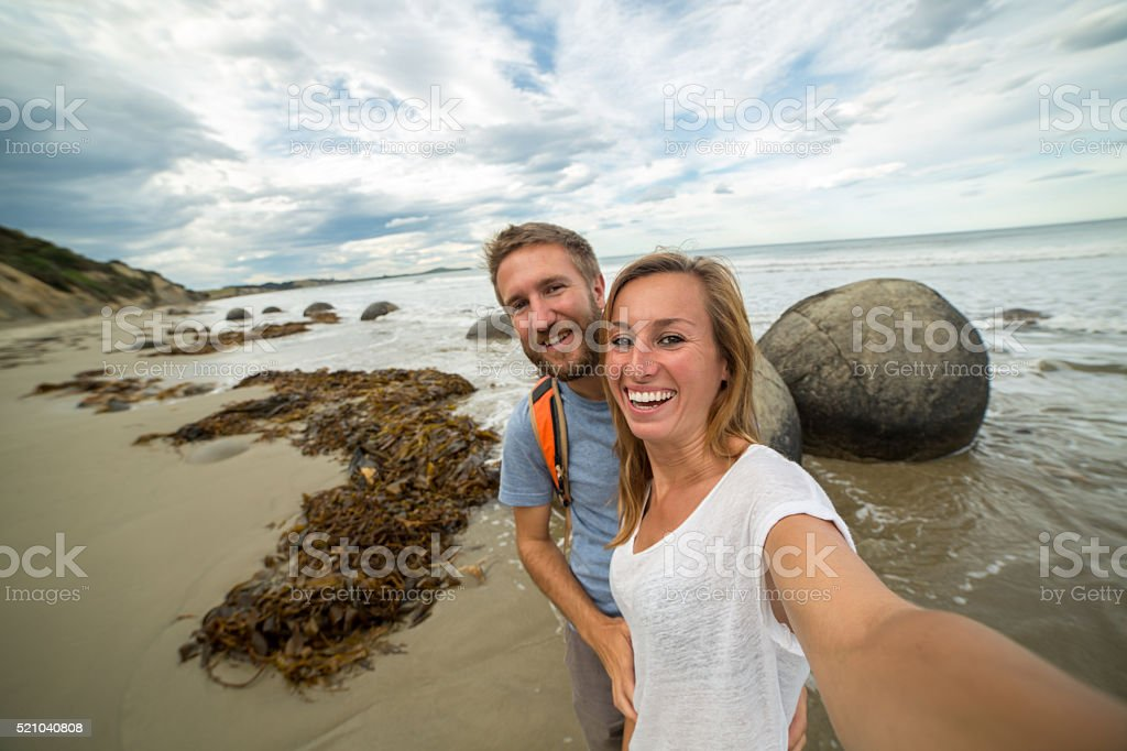 Two young adults take self portrait at spheric boulders-New Zealand stock photo