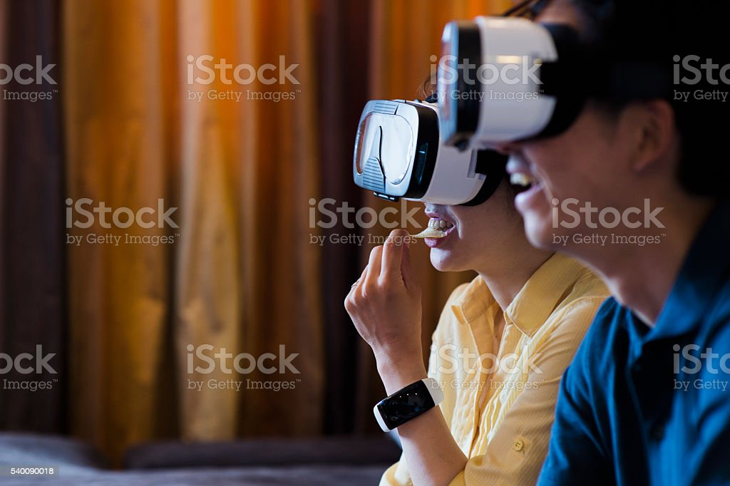 Two young adults trying out some virtual reality headsets stock photo