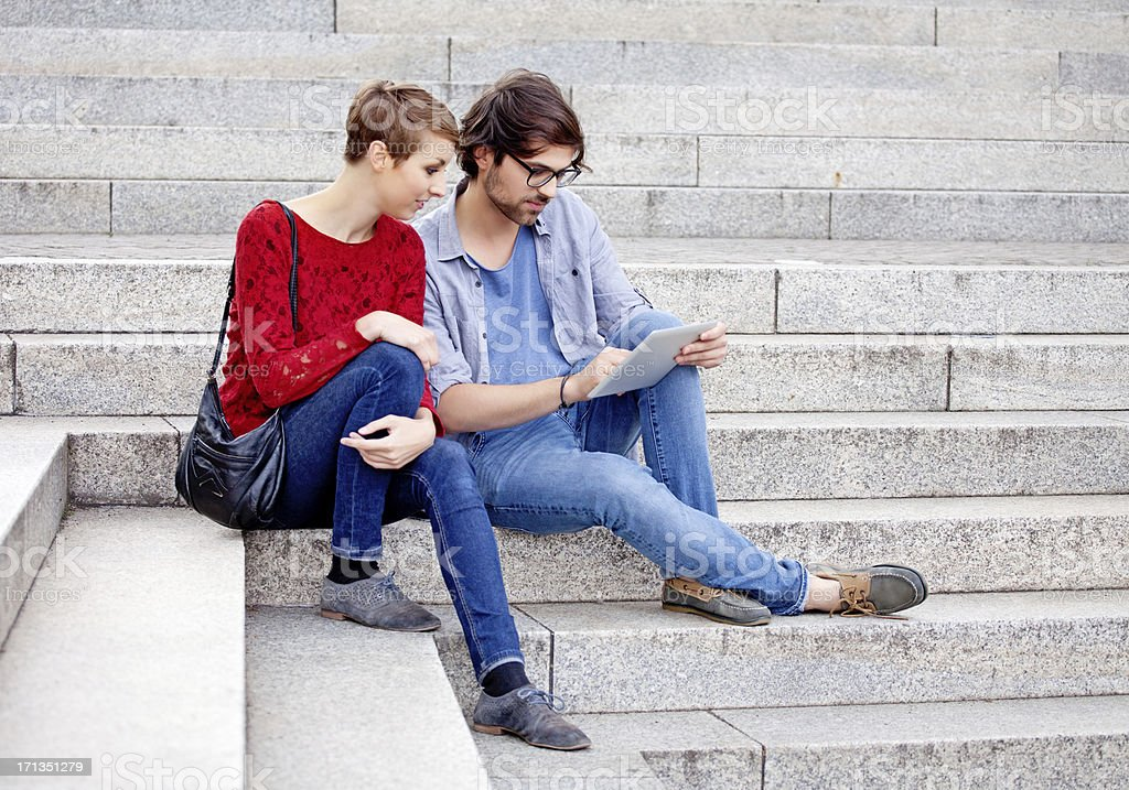 two young adults using digital tablet outdoors stock photo