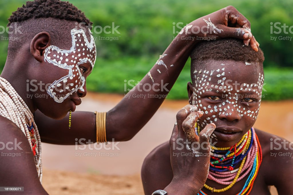 Two young African girls during face painting, Ethiopia. royalty-free stock photo