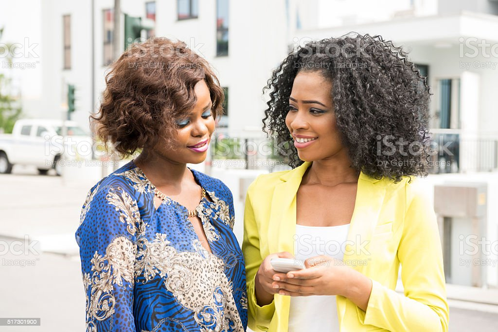 Two young African women with cell phone, smiling stock photo