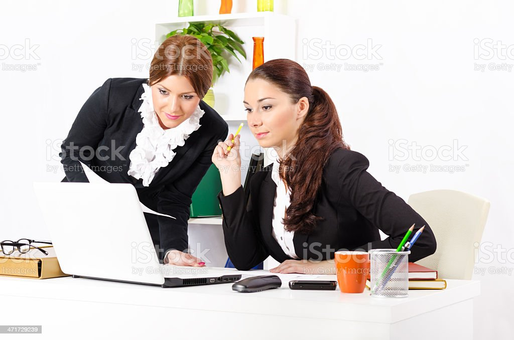 Two young and pretty businesswomen in their office working together royalty-free stock photo