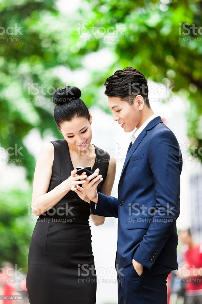Two Young Asian Adults Sharing Files Using NFC Technology stock photo