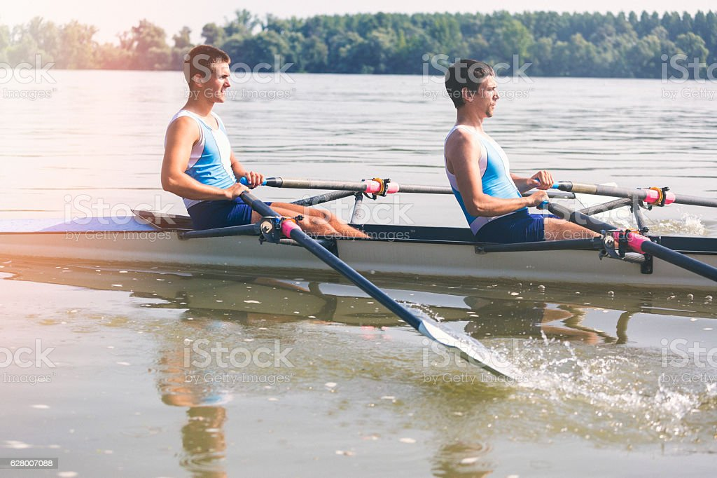 Two young athletes rowing on the river stock photo