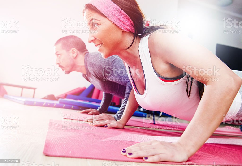 Two young athletes warming up and exercising push-ups in gym stock photo