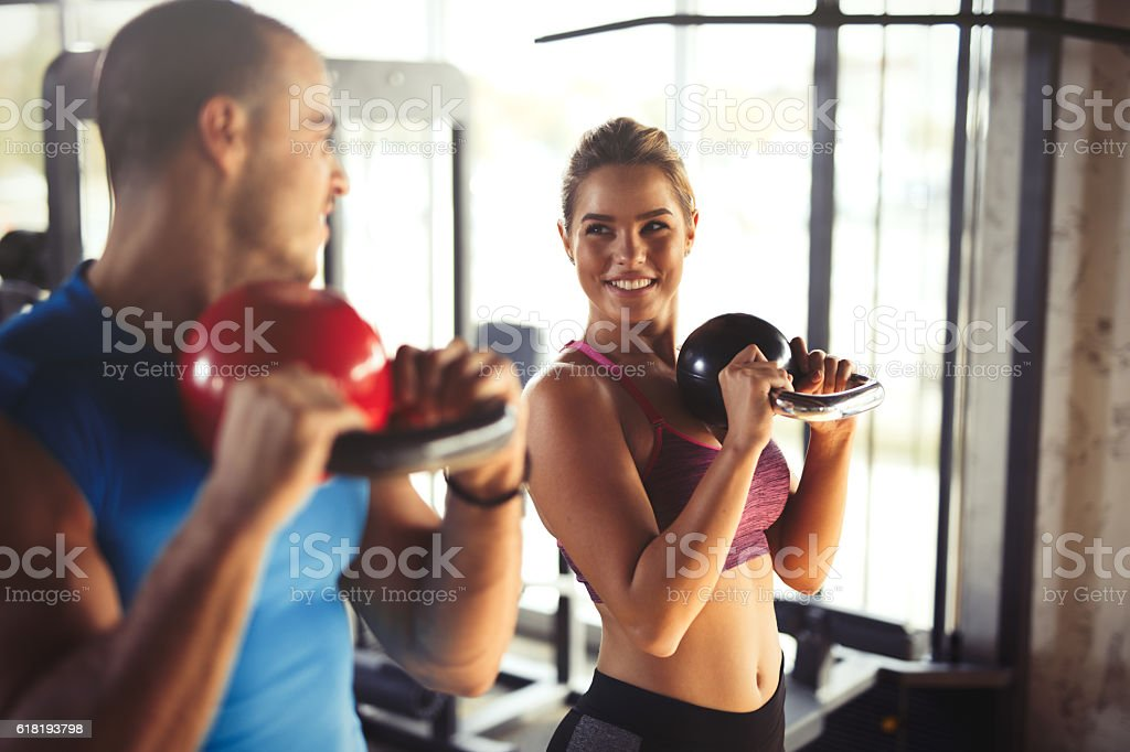 Two young athletic people doing kettlebell exercises at gym. stock photo