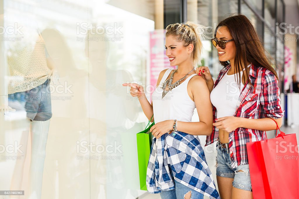 Two young attractive cheerful women are enjoying window shopping. stock photo