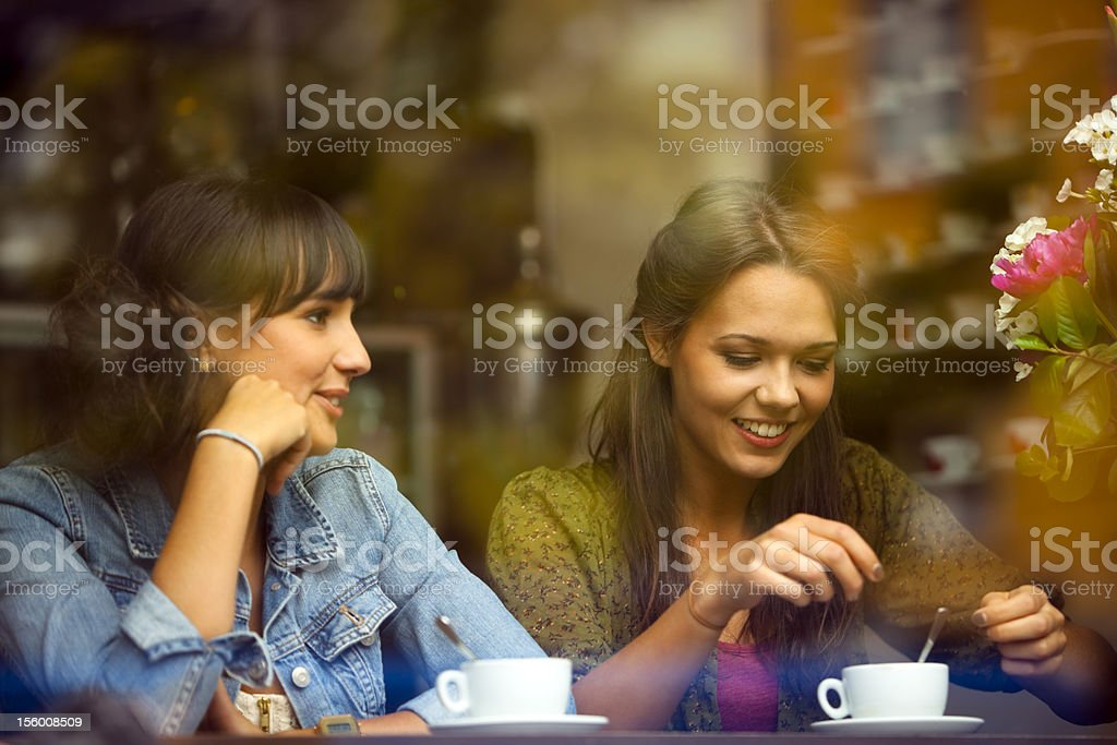 Two Young Beautiful Women Sitting in a Cafe stock photo