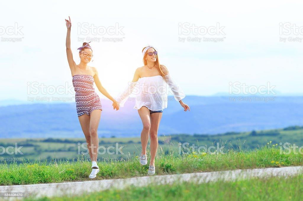 Two young boho women having fun on the road stock photo