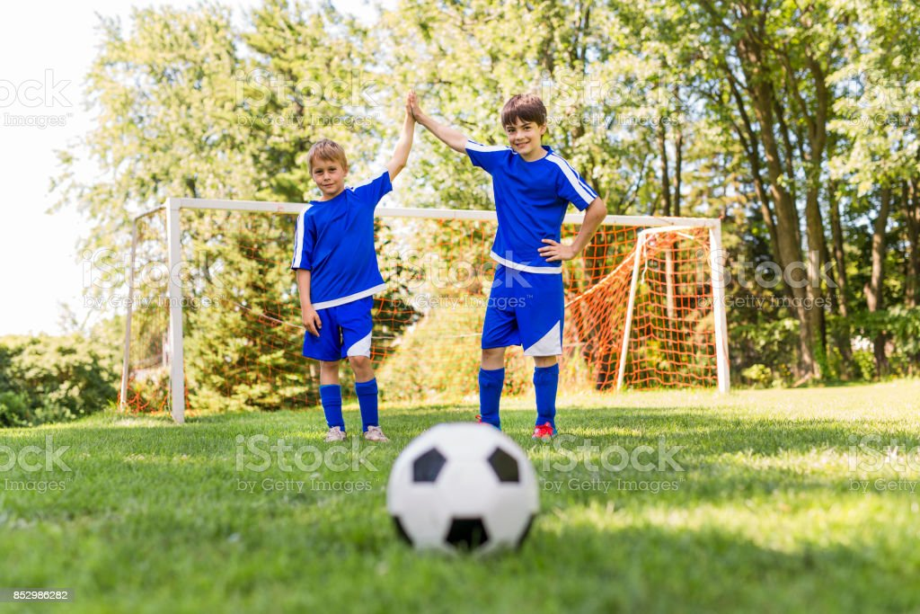 Two nice Young boys with soccer ball on a sport uniform