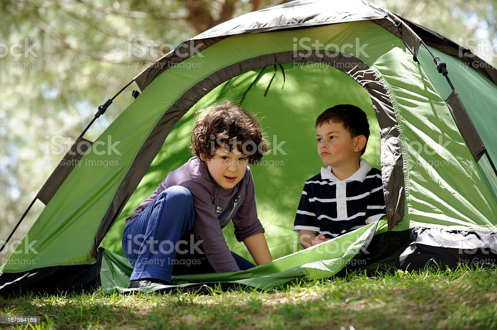 Two young boys in a green tent while camping  royalty-free stock photo