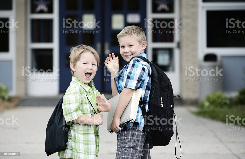 Two young boys in plaid wave as they go back to school royalty-free stock photo