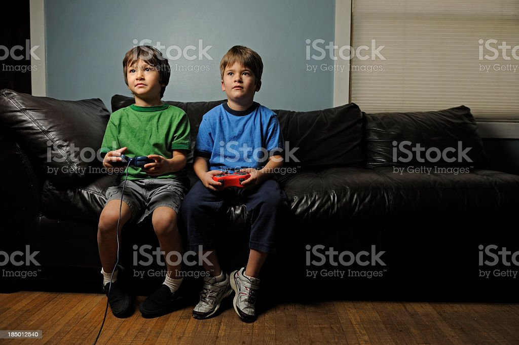 Two young boys on a leather couch playing video games stock photo