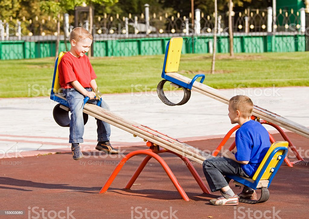 Two young boys on a seesaw in the park stock photo