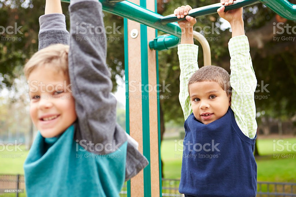 Two Young Boys On Climbing Frame In Playground stock photo