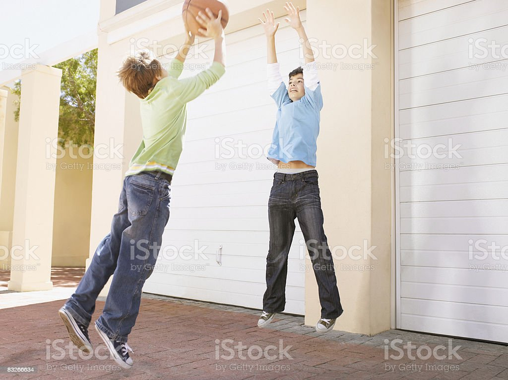 Two young boys playing basketball royalty-free stock photo