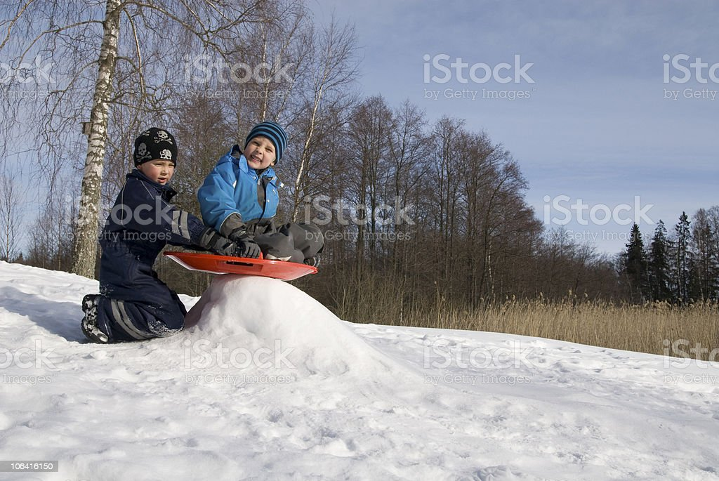 Two young boys playing with a sled royalty-free stock photo