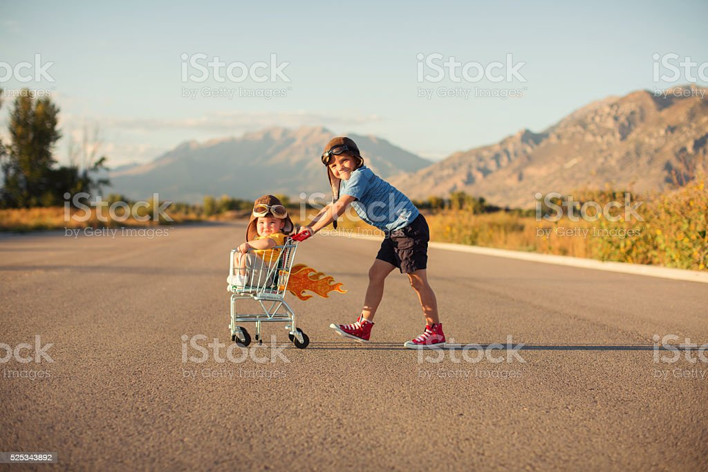 Two Young Boys Racing Shopping Cart stock photo