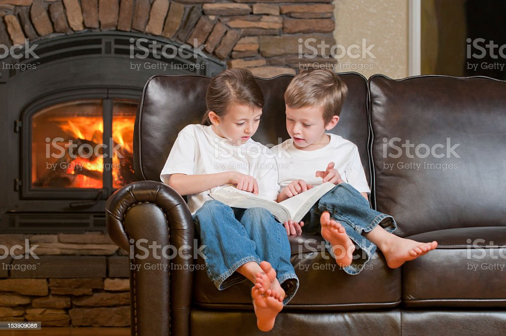 Two young boys reading by the fireplace royalty-free stock photo