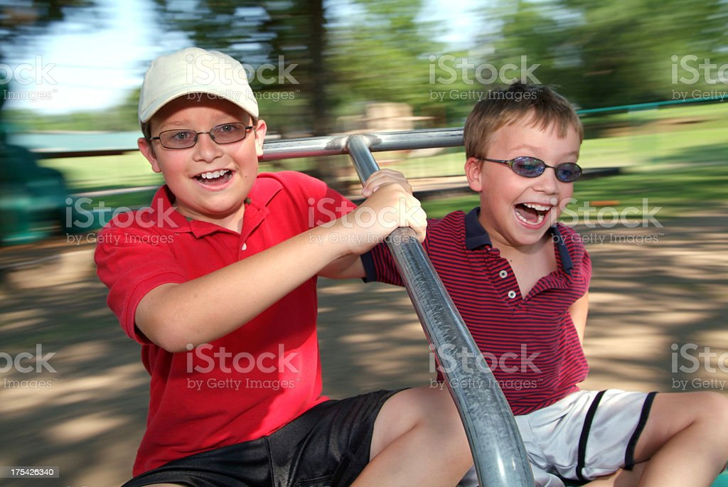 Two Young Boys Spinning Fast on a Merry Go Round stock photo