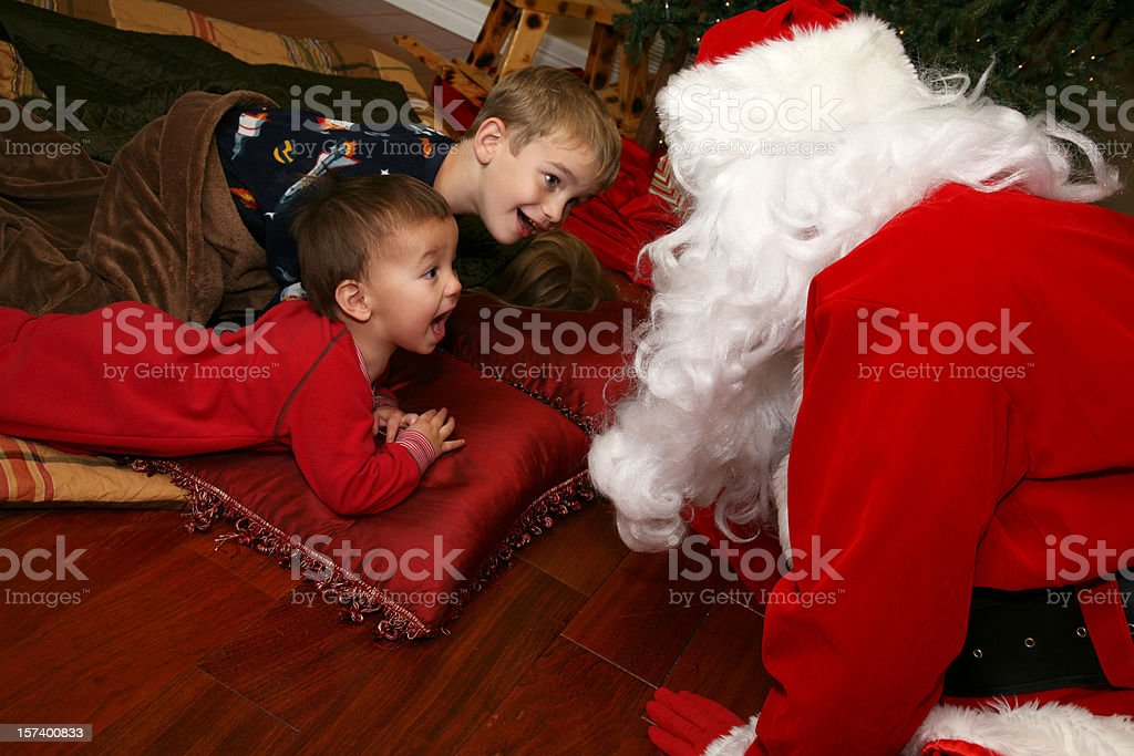 Two Young Boys Surprised By Santa In Their Living Room royalty-free stock photo