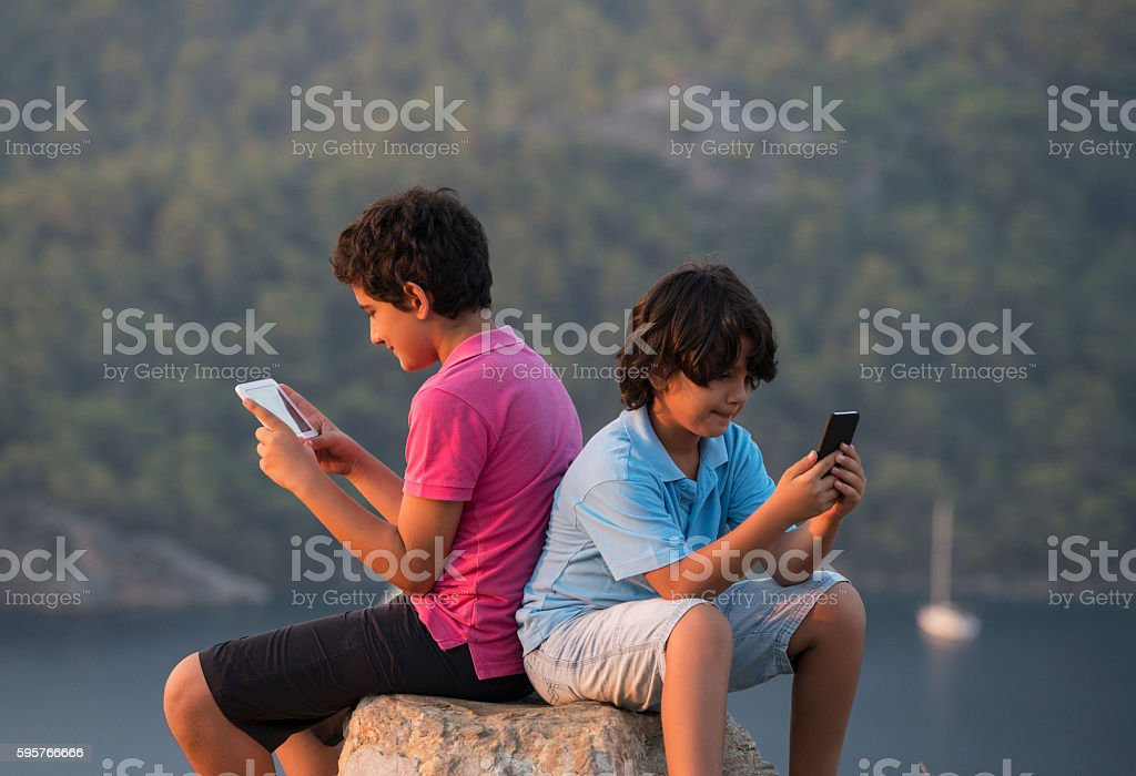 Two young boys using smartphone outdoors stock photo