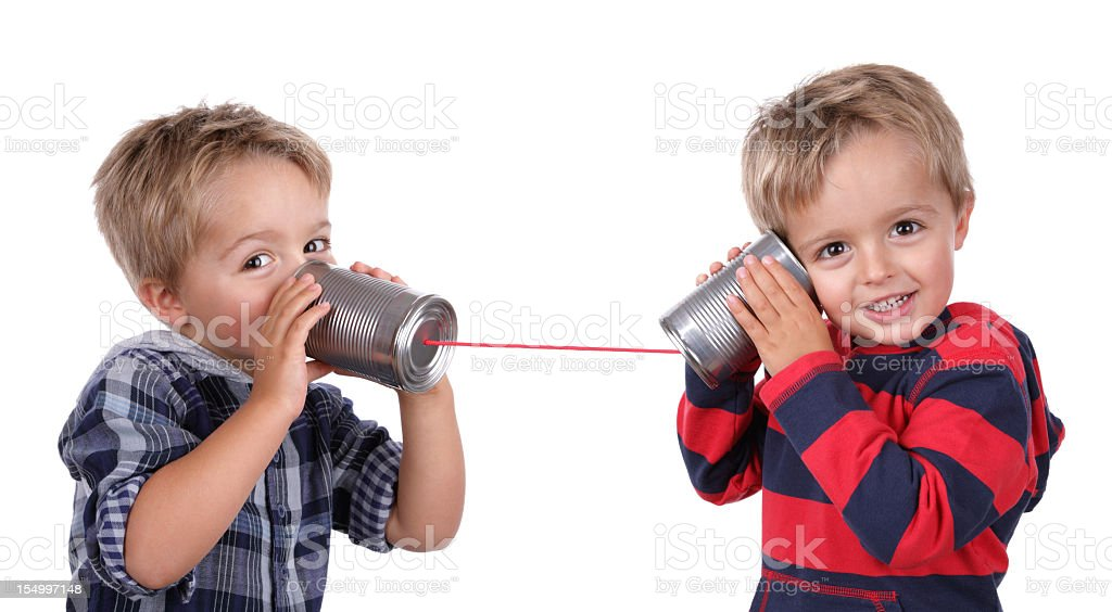 Two young boys using tin cans and a string as a telephone stock photo