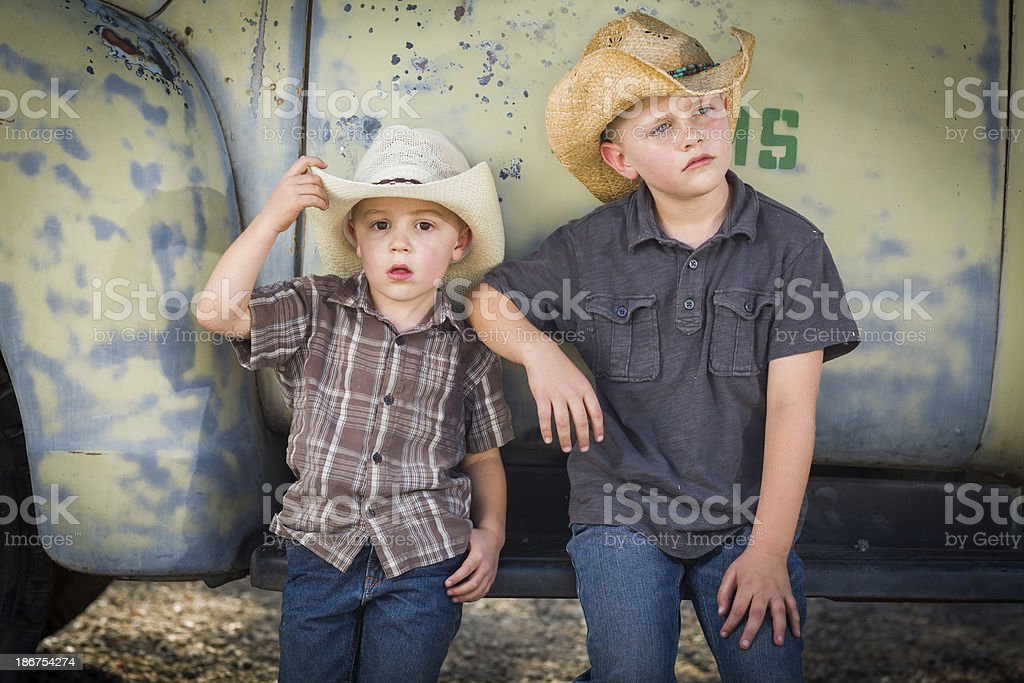 Two Young Boys Wearing Cowboy Hats Leaning Against Antique Truck royalty-free stock photo