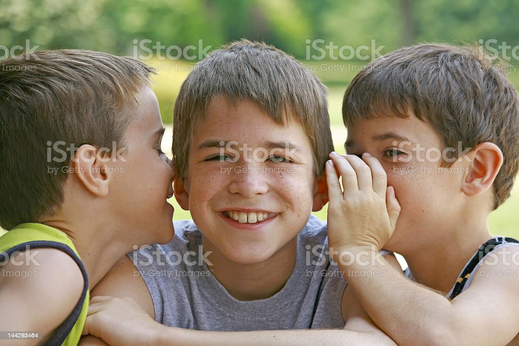 Two young boys whisper into another smiling boy's ears stock photo