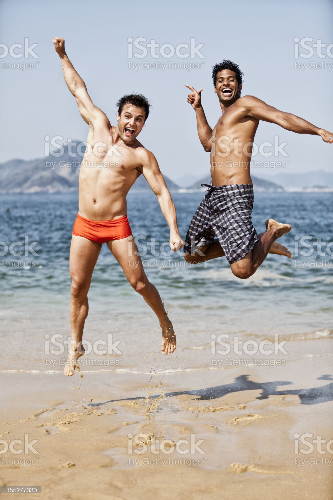 Two young brazilian man jumping on the beach royalty-free stock photo