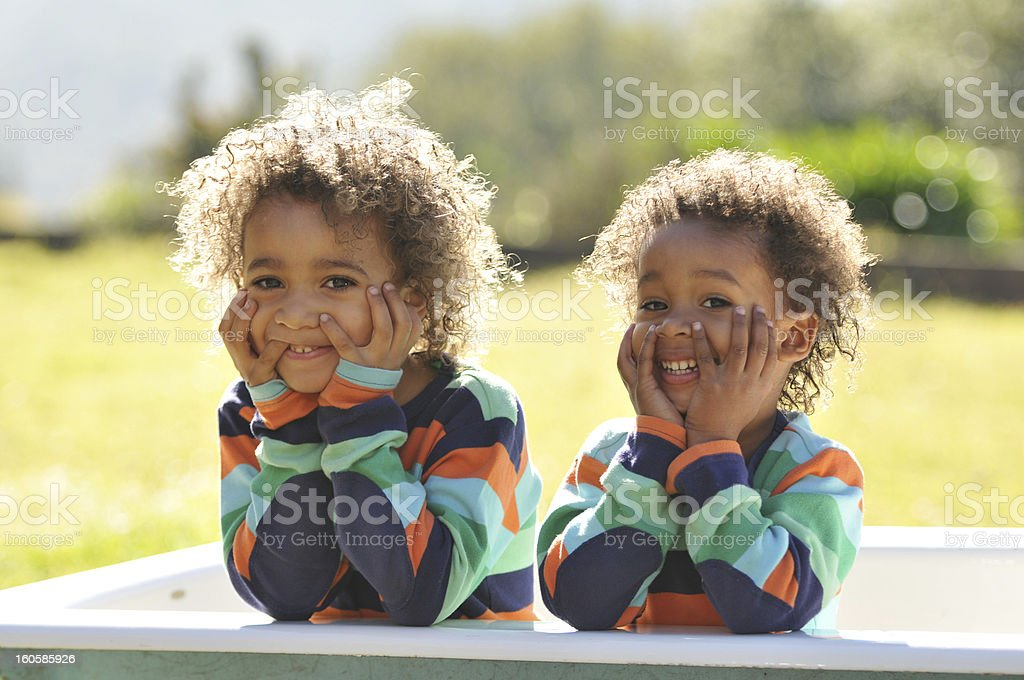 Two young brothers dressed alike taking photo outside in tub stock photo